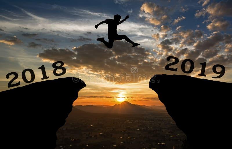 一个年轻人在2018年和2019年之间跳在太阳和通过在小山剪影空白  库存照片