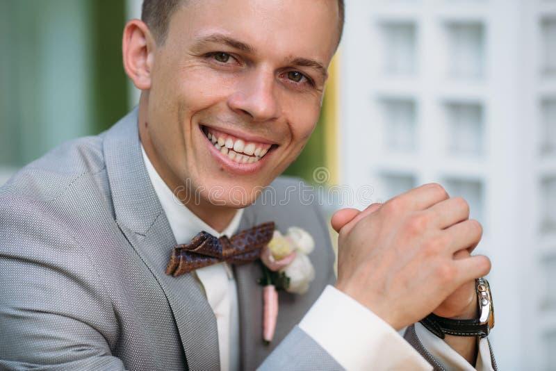 一个年轻人微笑的时髦的人的画象一套经典西装的在与一件白色衬衣和蝶形领结的灰色 一个新人 库存图片