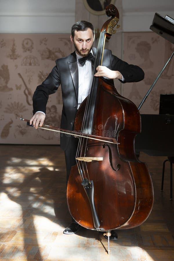 一个年轻人播放一个低音提琴 免版税图库摄影