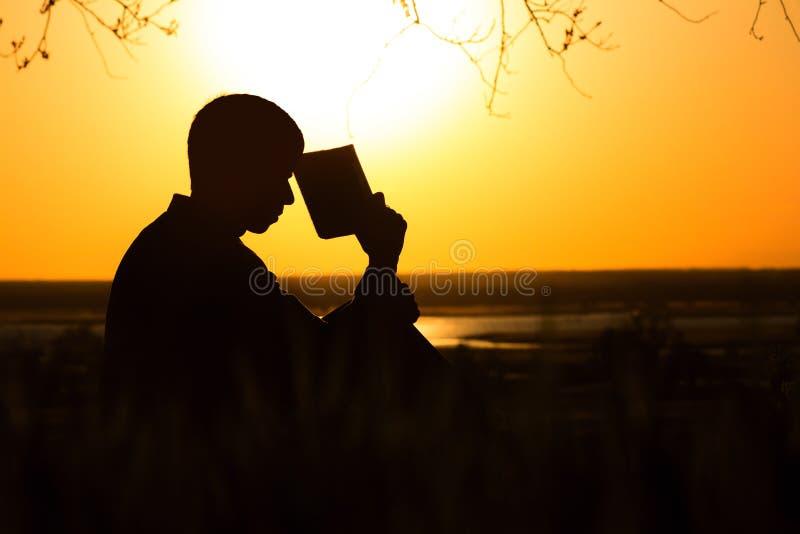 一个年轻人的剪影有圣经、男性祈祷对上帝的本质上,宗教的概念和灵性的 图库摄影