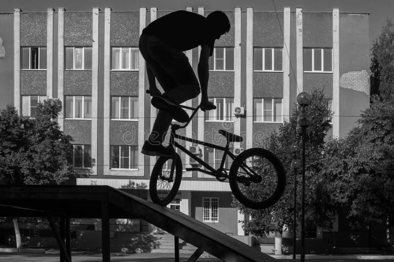 一个年轻人的剪影BMX的,做在skatepark舷梯的一个复杂的把戏 极端循环的Footjam Tailwhip 库存图片