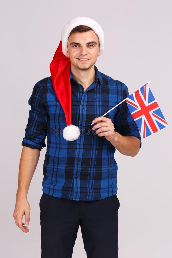一个年轻人的画象一个圣诞老人帽子的,有英国的旗子的在他的手上 免版税库存图片