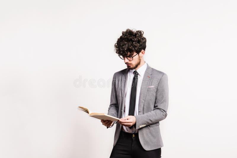 一个年轻人的画象有一本书的在白色背景的一个演播室 免版税库存照片