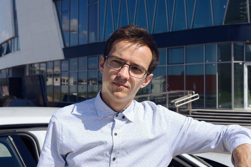 一个年轻人的画象玻璃的在汽车附近的一件衬衣 免版税库存图片