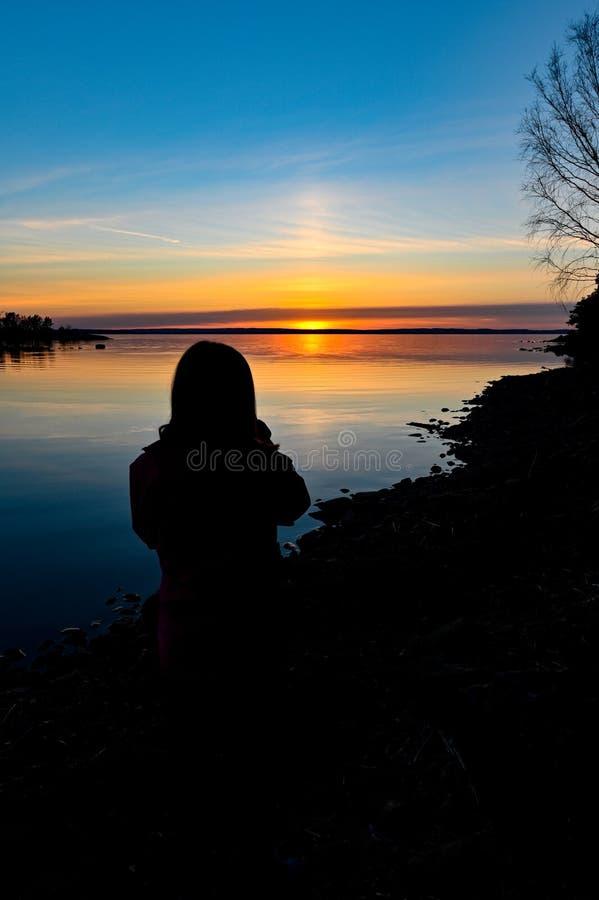 一个年轻人身分的Siluette在日落前面的 库存照片