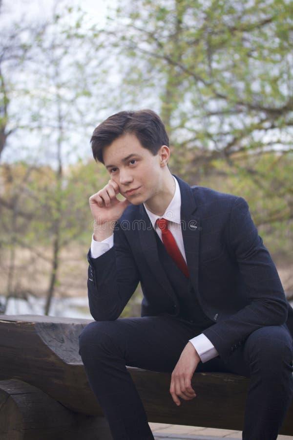 一个年轻人,一个少年,一套经典衣服的 坐一个长木凳在春天公园 他考虑,扶植他的头用h 免版税库存照片
