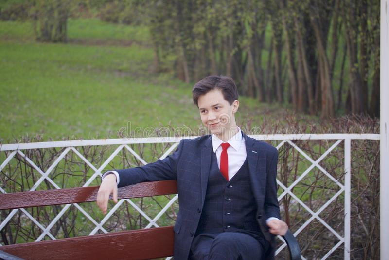一个年轻人,一个少年,一套经典衣服的 坐葡萄酒长凳在春天公园 免版税库存照片