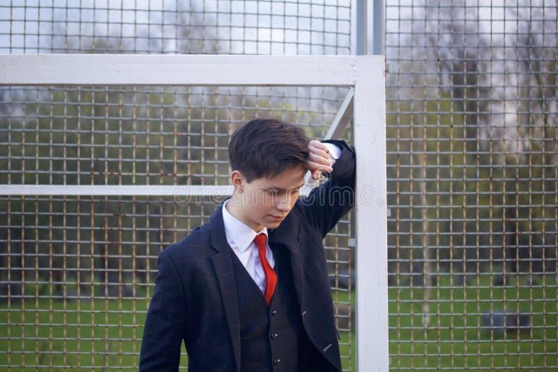 一个年轻人,一个少年,一套经典衣服的 它在橄榄球目标 他倾斜了反对酒吧用他的手,并且放置了他的头 免版税图库摄影