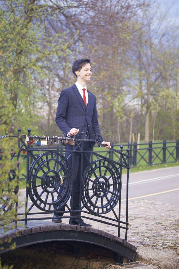 一个年轻人,一个少年,一套经典衣服的 它在葡萄酒桥梁站立在公园,投入他的手在栏杆和喜悦 图库摄影