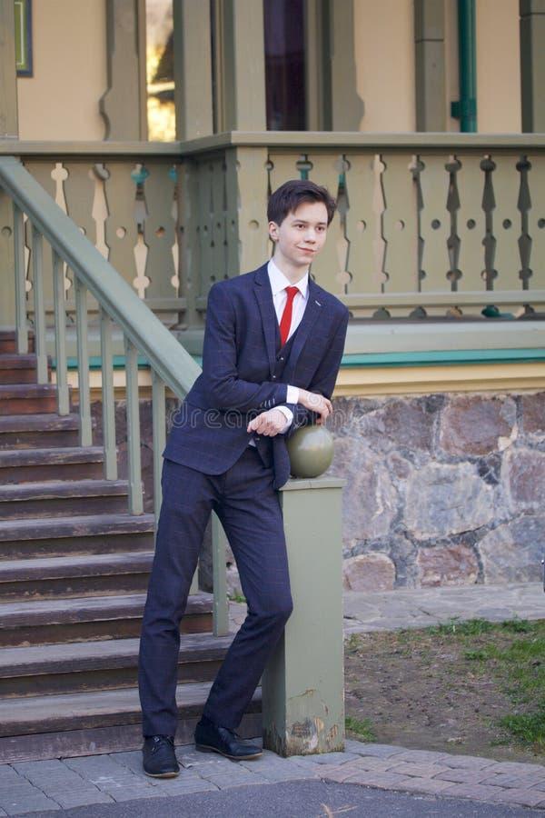 一个年轻人,一个少年,一套经典衣服的 它站立,倾斜在一个木楼梯的栏杆 库存照片