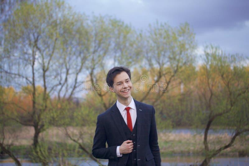 一个年轻人,一个少年,一套经典衣服的 走沿春天公园的大道 免版税库存图片