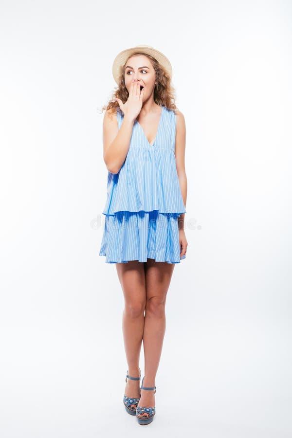 一个年轻俏丽的女孩的全长画象在白色背景和帽子的震惊隔绝的夏天礼服 免版税库存图片