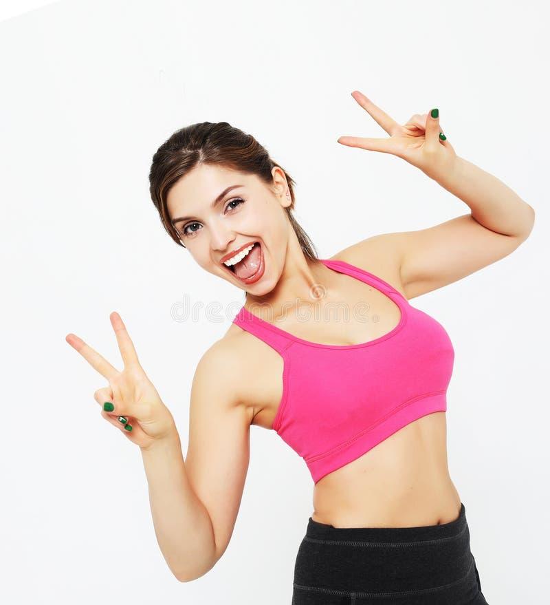 一个年轻健身妇女陈列的画象好在白色背景隔绝的标志,体育概念 免版税库存照片