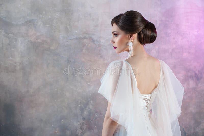 一个年轻典雅的深色的新娘的画象有一种时髦的发型的 免版税库存图片