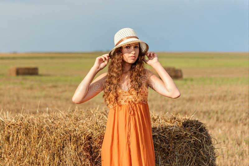 一个年轻卷曲女孩和在一块被收获的麦田的葡萄酒sundress的画象一个减速火箭的帽子的 库存照片