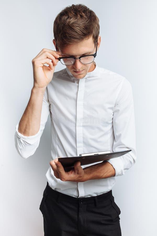 一个年轻可爱的人的画象玻璃的,在一件白色衬衣,有一个文件夹在他的手上和看的她,隔绝在丝毫 免版税库存图片