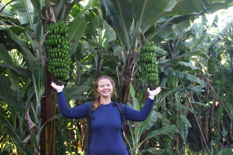一个年轻可爱的女性旅客在香蕉棕榈旁边站立 库存照片
