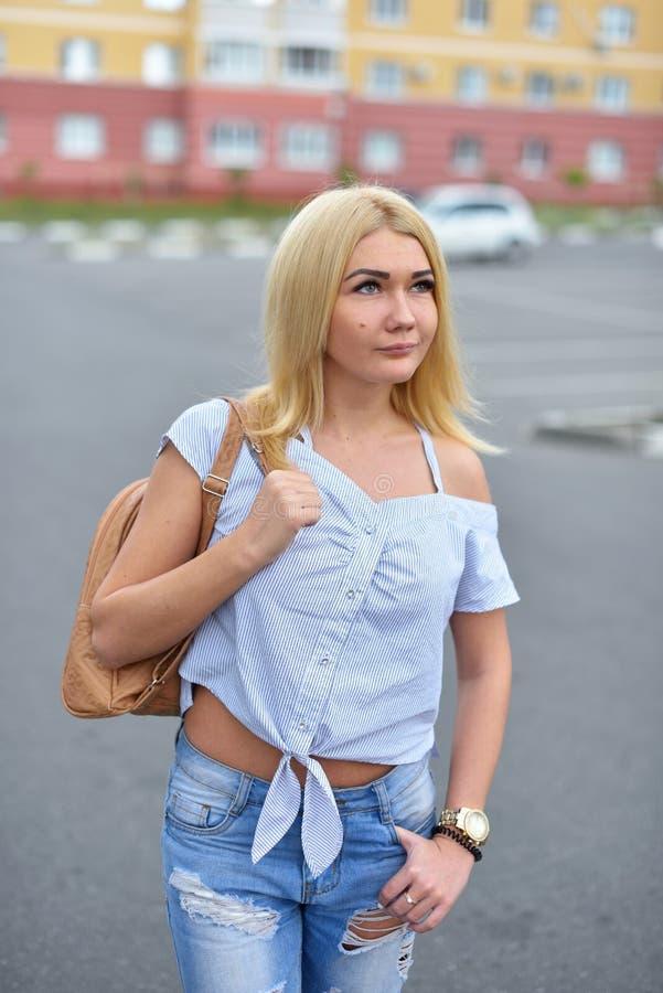 一个年轻和愉快的白肤金发的女孩在染她的头发以后,步行沿着向下有一个背包的街道在被撕毁的蓝色牛仔裤和微笑 免版税库存图片