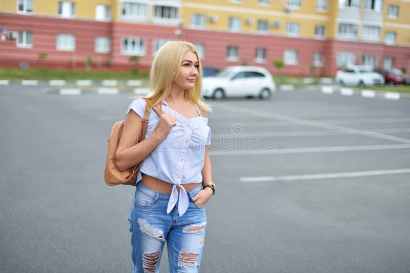 一个年轻和愉快的白肤金发的女孩在染她的头发以后,步行沿着向下有一个背包的街道在被撕毁的蓝色牛仔裤和微笑 图库摄影
