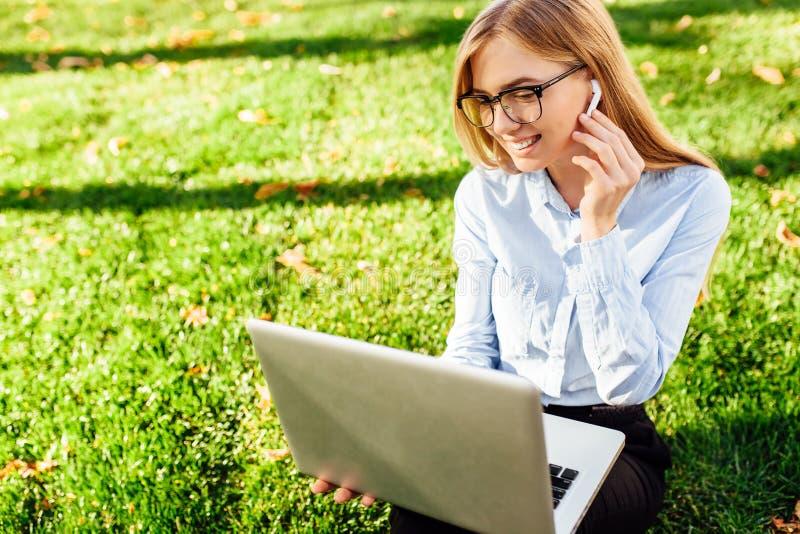 一个年轻女商人戴着眼镜的画象,坐绿草在公园,工作使用膝上型计算机和无线headph 库存照片