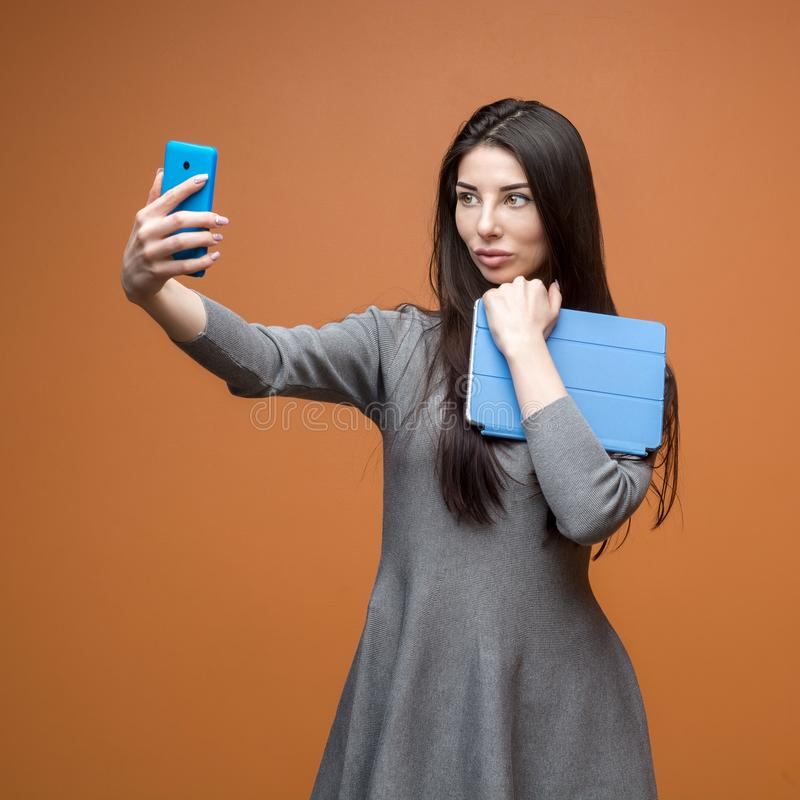 一个年轻女商人的画象灰色礼服的有蓝色做selfie和看在电话的智能手机和片剂的 图库摄影