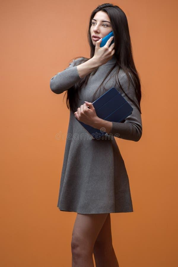一个年轻女商人的画象灰色礼服的有蓝色打电话的智能手机和片剂的对橙色墙壁 免版税库存照片