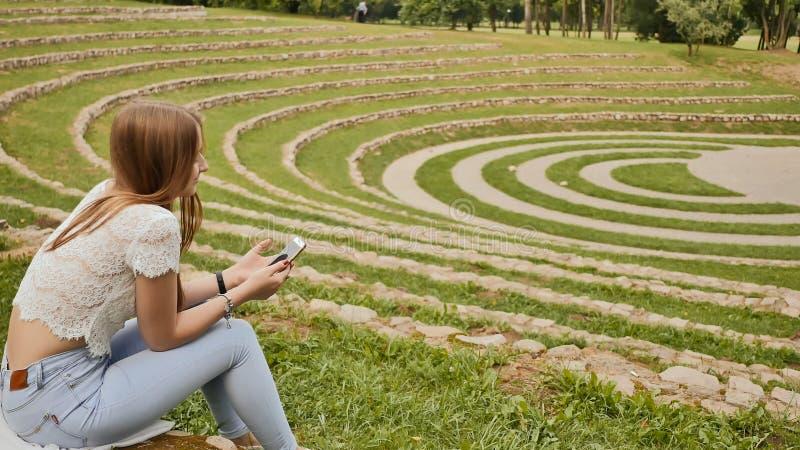 一个年轻女学生在她的手上在体育场的边缘坐草并且拿着一个手机 休息在期间 库存照片