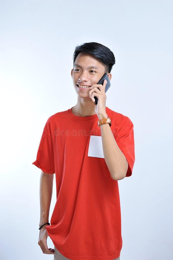 一个年轻学生亚裔人的画象谈话在手机,讲话幸福微笑 库存照片