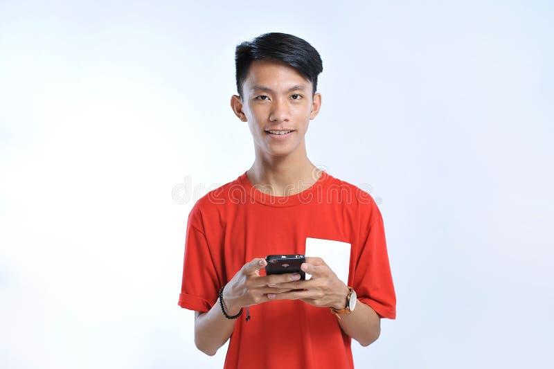 一个年轻学生亚裔人的画象谈话在手机,讲话幸福微笑 免版税库存图片