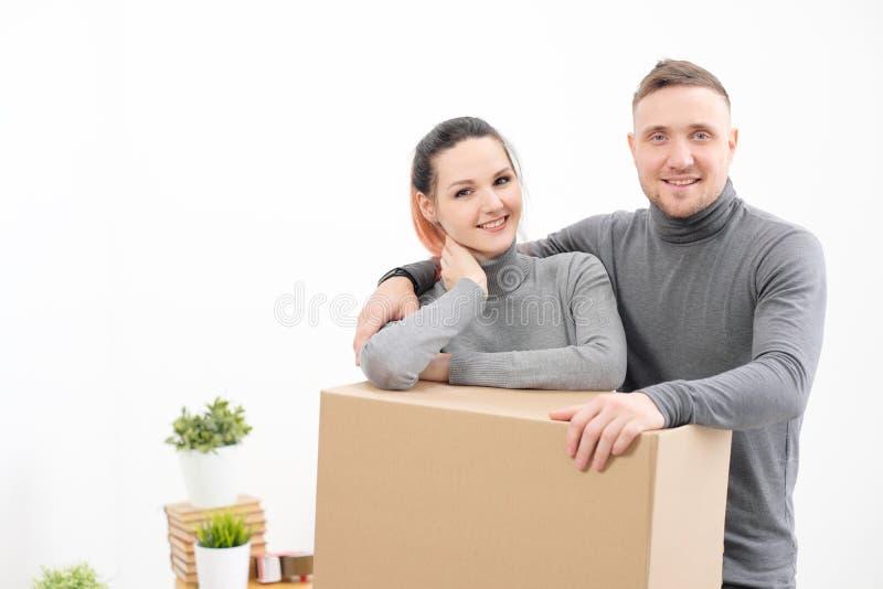 一个年轻家庭、一个男人和一名妇女灰色毛线衣的移动向新的公寓 有货物的箱子在白色 库存照片