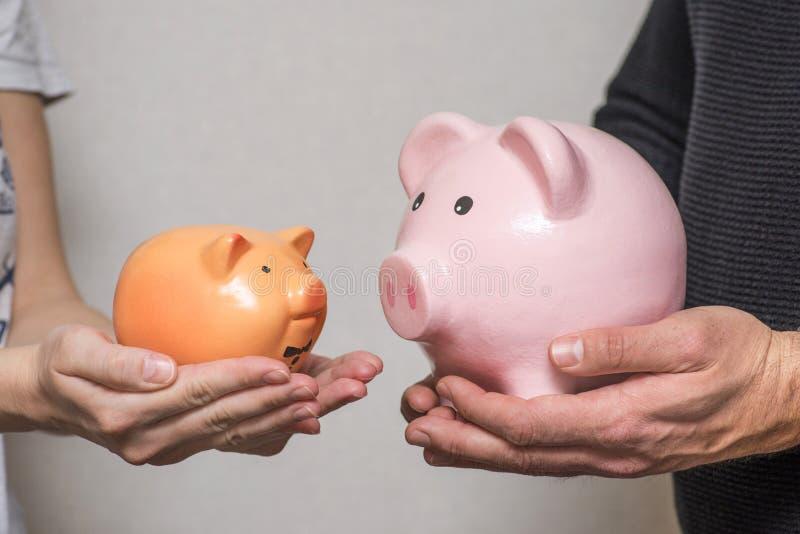 一个年轻家庭丈夫和妻子拿着显示他们的对家庭的贡献的水平不同的大小存钱罐  图库摄影