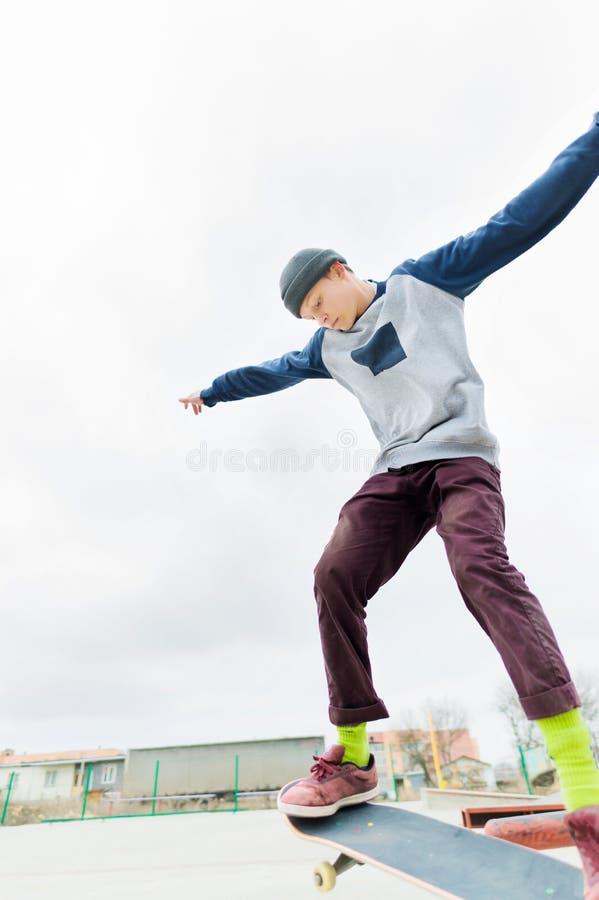 一个年轻少年,溜冰板者,做在栏杆的一个把戏在skatepark 青年体育的概念在都市的 图库摄影