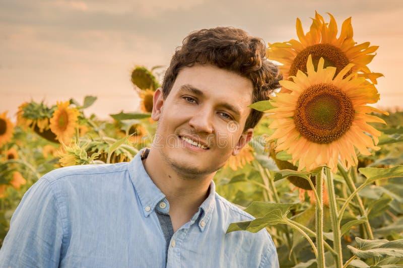 一个年轻微笑的人的画象的关闭向日葵的领域的 反对落日和橙色花的backdground 免版税库存照片