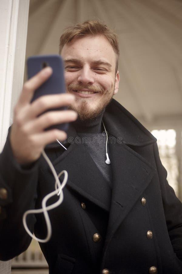 一个年轻微笑的人,20-29岁低角度射击,发短信给和使用他的智能手机 库存图片