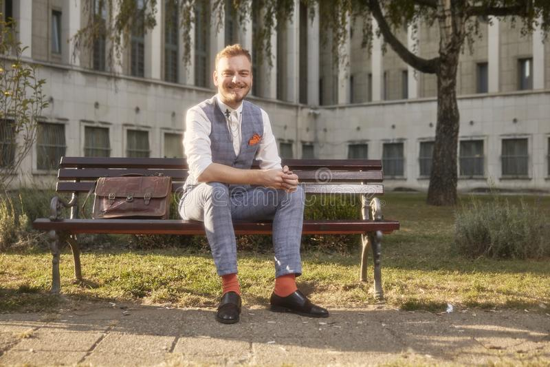 一个年轻微笑的人,20-29岁,佩带的行家减速火箭的衣服,坐在城市公园正方形的长凳 免版税库存照片