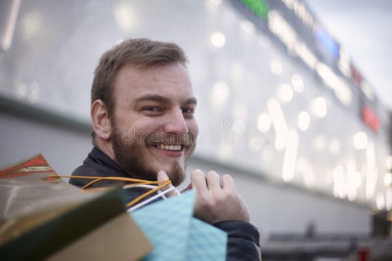一个年轻微笑的人,20-29岁,在他的运载的购物带来,看回到照相机 户外在购物前面 免版税库存图片