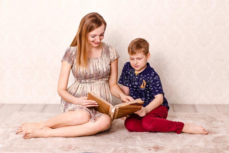 一个年轻微笑的母亲和七岁的儿子在屋子里一起观看一相册,坐地毯 库存照片