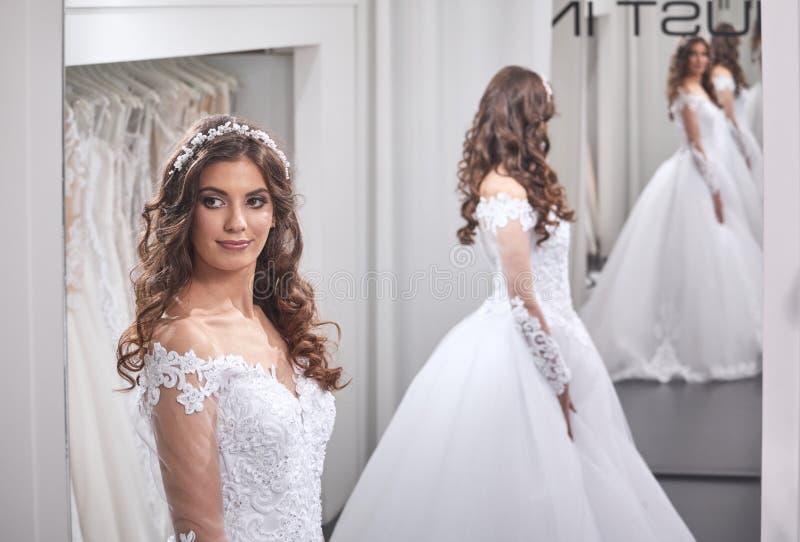 一个年轻新娘,看自已,佩带的褂子, 库存图片