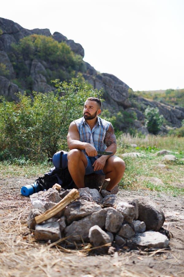 一个年轻旅客在阵营坐由火 有刀子的一个人放火对火 夏天室外休闲 库存照片