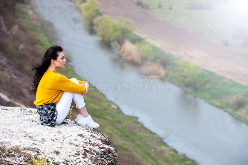 一个年轻旅客女孩坐谷上面  少女爱狂放的生活,旅行,自由 旅行旅游愉快的妇女 旅行和 库存照片