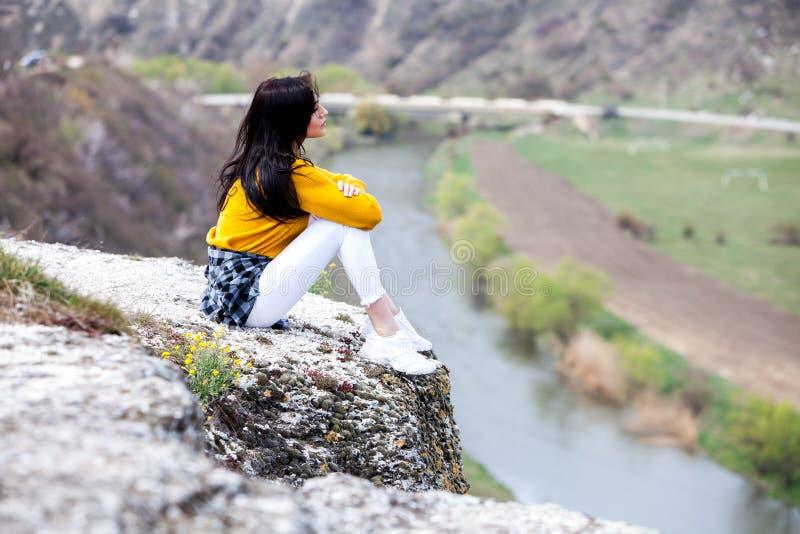 一个年轻旅客女孩坐谷上面  E 旅行旅游愉快的妇女 r 免版税库存图片