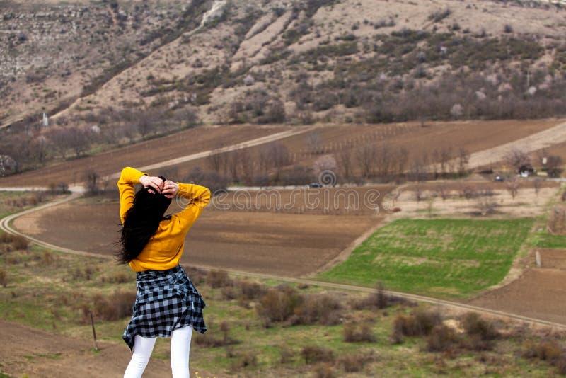 一个年轻旅客女孩坐谷上面  少女爱狂放的生活,旅行,自由 旅行旅游愉快的妇女 旅行和 免版税库存图片