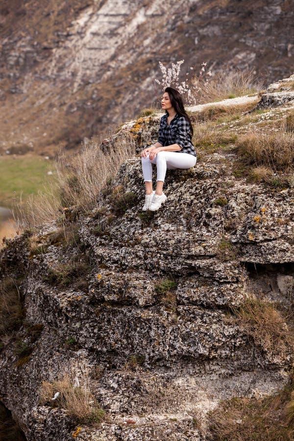 一个年轻旅客女孩坐谷上面  E 旅行旅游愉快的妇女 r 免版税库存照片