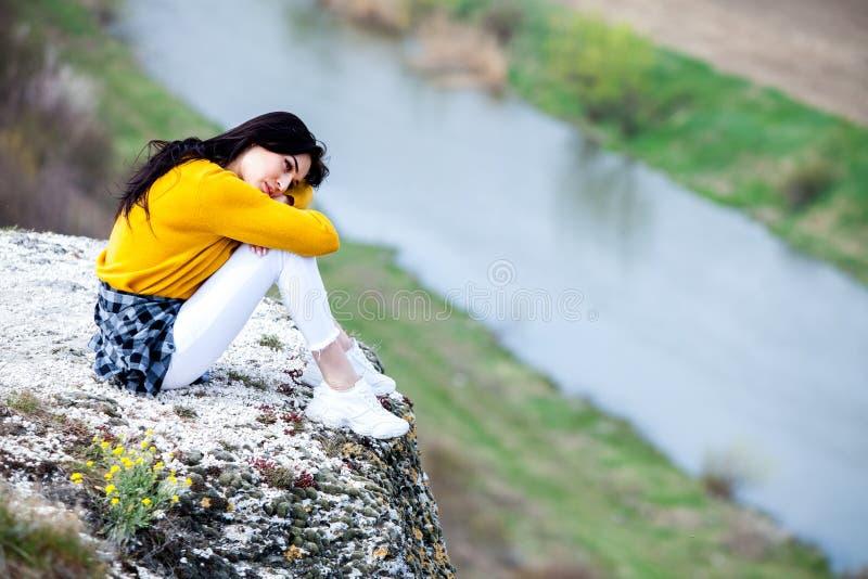 一个年轻旅客女孩坐谷上面  少女爱狂放的生活,旅行,自由 旅行旅游愉快的妇女 旅行和 免版税库存照片