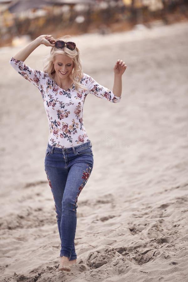 一个年轻无忧无虑的女孩,赤足,走的沙子海滩 全长射击,夏天 查找下来 免版税库存照片