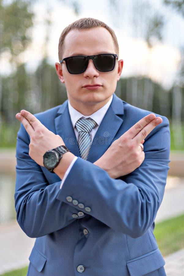 一个年轻有手指的商人耍笑的展示手枪的画象 免版税图库摄影