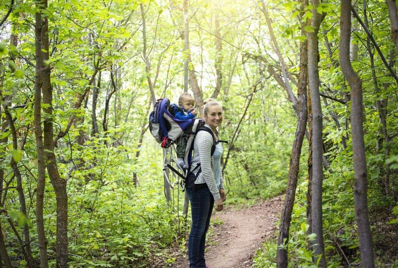 一个年轻母亲和她的儿子在山一起采取远足在一个美好的夏天晚上 在妈妈的逗人喜爱的年轻小儿子骑马 库存图片