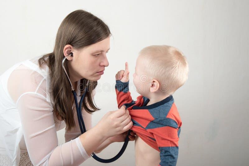 一个年轻母亲审查有听诊器的一个男孩 家庭医生 免版税库存图片