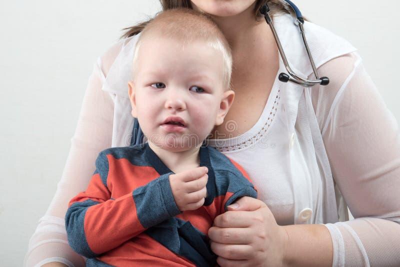 一个年轻母亲审查有听诊器的一个男孩 家庭医生 免版税库存照片