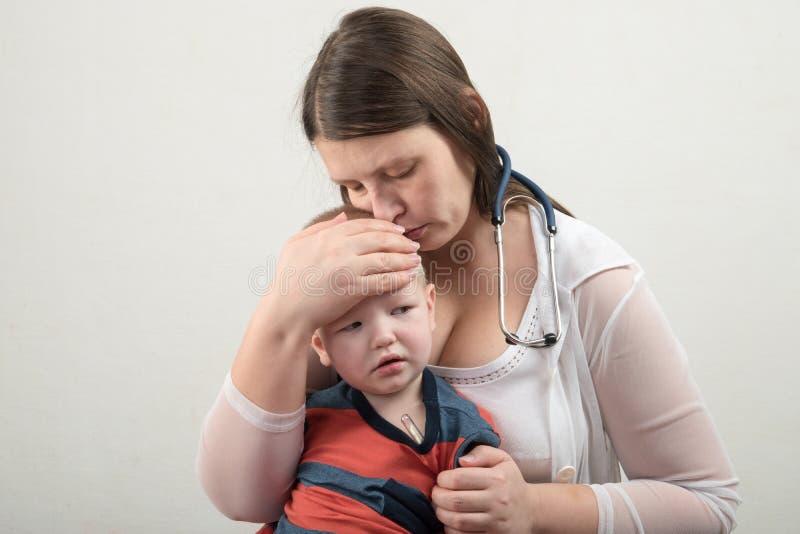 一个年轻母亲审查有听诊器的一个男孩 有听诊器的女性医生在医院 专业医学诊所 免版税库存图片